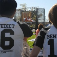 Two students wearing Campus Ministry Pope Benedict baseball t-shirts look on while Pope Benedict XVI holds mass in Washington, DC
