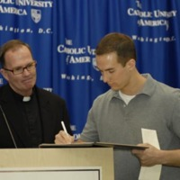Father O'Connell looks on as Osgood signs the official copy of his winning essay