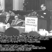Msgr. George G. Higgins (at podium) with labor leader George Meany (immediate left, seated), at a press conference for the Coalition for a Fair Minimum Wage, 1977.