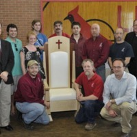 CUA's student designers gather around the papal chair with the volunteers from Jefferson Millwork who helped build the chair.
