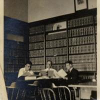 Three men at a table in McMahon Library